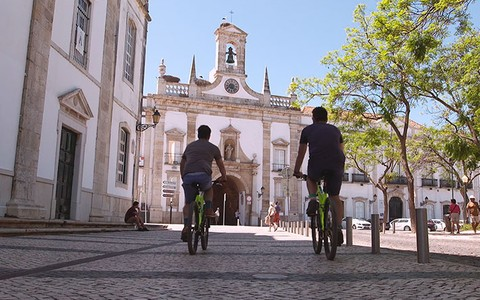 Tom and Henry strolling through Faro on bikes